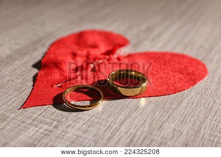 Torn fabric heart and wedding rings on wooden background. Relationship problems