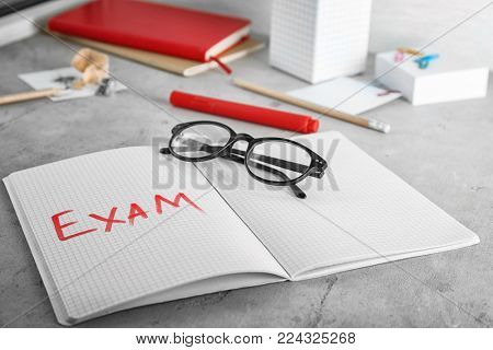 Word EXAM written in notebook on table