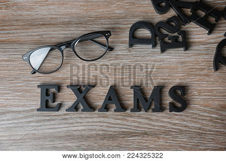 Word EXAMS made of letters on wooden background