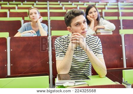 Students sitting together with boredom in university lecture hall