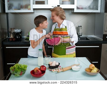 Grandmother with grandchild baking cookies prepare doughi in the kitchen together