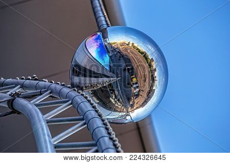 A ball on a building facade reflecting a 360 degree panorama of the surroundings.