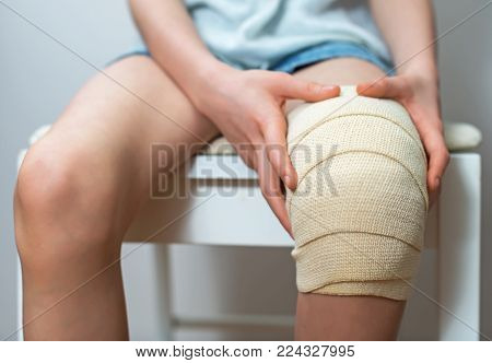 Child knee with adhesive and gauze bandage. poster