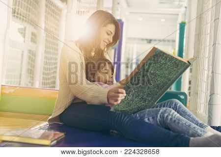 Mother and daughter sitting in a playroom, reading a fairy tale; daughter sitting in mother's lap