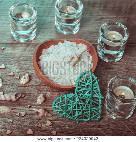 Spa concept in Valentine's Day, candles, handmade heart, seashells, setting for aroma therapy and salt massage on bed, relax and healthy care. Rustic style. Toned image in chocolate, aquamarine tones.