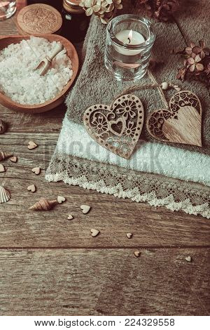 Spa concept in Valentine's Day, candles, handmade heart, seashells, setting for aroma therapy and salt massage on bed, relax and healthy care. Rustic style. Toned image in chocolate, tones.