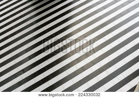 Abstract geometric pattern of regular alternating black and white stripes of tiles on the floor. Top view.