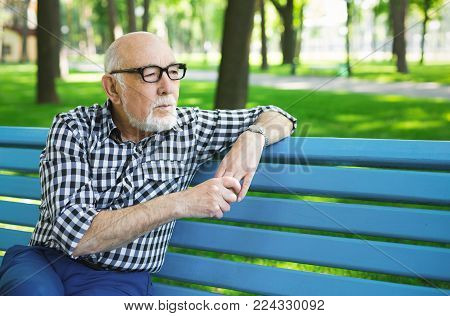Pensive senior man outdoors. Elderly man in casual, wearing eyeglasses, sitting on the bench in sunny park, copy space