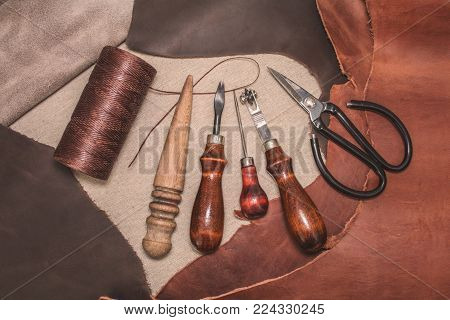 Tools for leather crafting and pieces of brown leather. Manufacture of leather goods. View from above