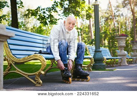 Active senior man. Elderly man bent over to lace up his roller skates. Healthy lifestyle and sporty old age concept, copy space