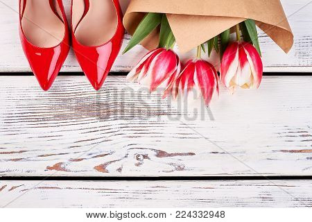 Cropped shot of red pump shoes and flowers on wooden table. Tulip bouquet in craft paper wrapping. Gifts from husband.