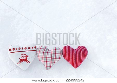 3 Three white hearts with winter cross stitch deer in red on snow. Scandinavian Norwegian styled Christmas stitching knitting pattern on snowflakes
