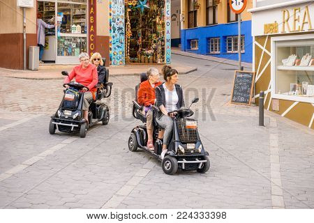 Benidorm, Spain - January 29, 2018: Womans using hired mobility scooters in the street of Benidorm, Costa Blanca, Spain