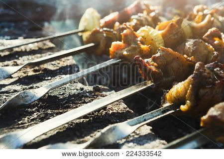 Street fast food festival. Cooking raw kebab on metal skewer. BBQ fresh beef chop slices. Traditional eastern dish, shish kebab.