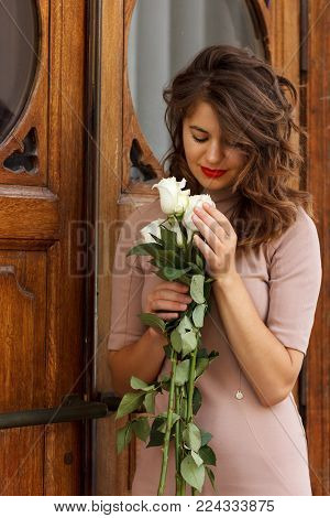 Portrait of beautiful woman with white roses standing near an ancient wooden door