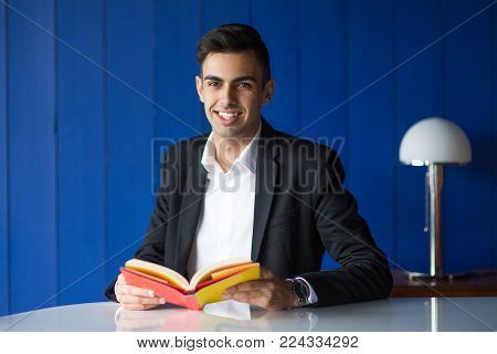 Positive intelligent student reading book in cozy library and looking at camera. Happy confident young man getting new knowledge from literature. Marketing book concept
