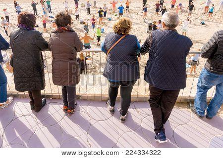 Benidorm, Spain, January 29, 2018: Elderly people watch how active seniors are doing sports exercises on the beach in Benidorm, Alicate, Spain