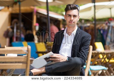 Serious handsome businessman resting in sidewalk cafe. Calm fashionable male trader reading newspaper analyzing stock market while sitting in summer cafe. Analyst concept
