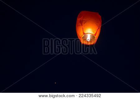 Beautiful orange paper sky lantern shot against the night sky. These small paper bags with a small candle underneath fly beautifully. They've become traditional during the indian festival of Makar Sankranti in Rajasthan