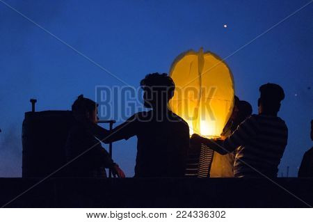 Silhouette of people standing together and flying a paper sky lantern which is lit. These lanterns have become traditional during the indian festival of makar sankranti or uttaryan in Jaipur India