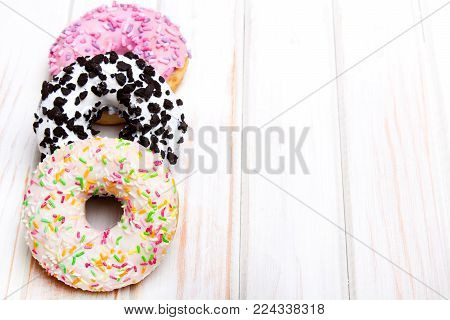Traditional donuts on white wooden background.  Tasty doughnuts with icing, copy space