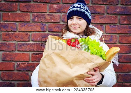 Beautiful girl with package of food products near supermarket. woman shopping at grocery store. Lady in warm clothes and hat holding grocery shopping bag with vegetables.