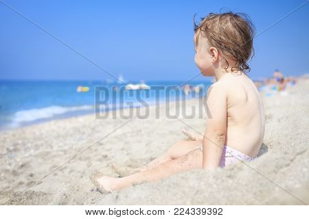 Little child on sandy beach of sea looking at waves. Child on the sea on clear sunny day. Relax on the beach with children. Kid on white sand on the beach