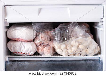 Assortment of frozen meat and dumplings in home fridge
