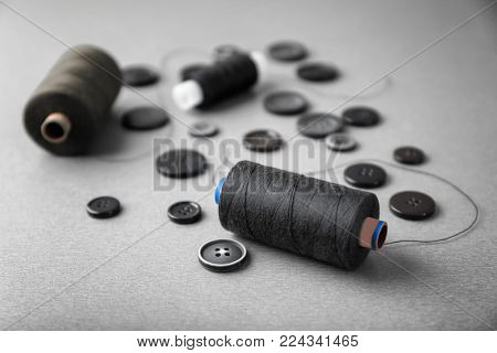 Dark sewing threads with buttons on grey background