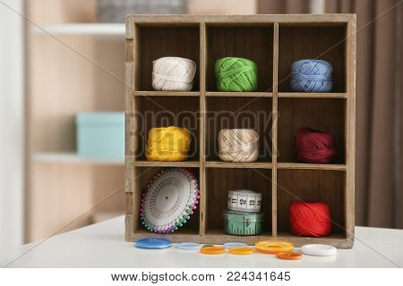 Wooden compartment box with crocheting clews and accessories on table indoors