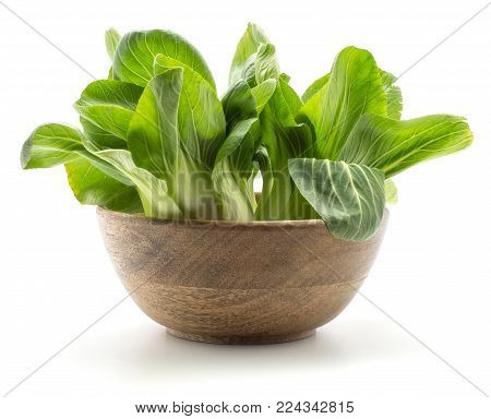 Fresh bok choy (Pak choi) in a wooden bowl isolated on white background