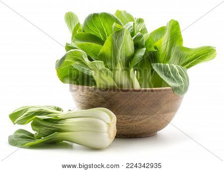 Fresh bok choy (Pak choi) in a wooden bowl one cabbage is near isolated on white background
