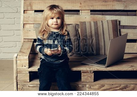 Kid at computer with cell phone, sms and 4G. Social network and new technology. child with laptop and mobile phone, education. Small boy blogging on bench, online buy. School and communication.