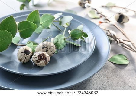 Eucalyptus twigs and quail eggs on plate as decor for Easter table setting
