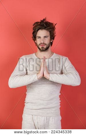 Insomnia, energy, single with uncombed hair. Morning wake up, everyday life. Sleepy man with beard on red background. Man with disheveled hair in underwear. Meditation, Barber and hairdresser.