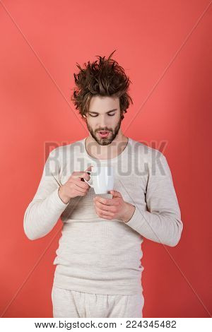 Sleepy guy with tea cup on red background. Man with disheveled hair drink mulled wine. Insomnia, refreshment and energy. Cold and flu, single. Morning with coffee or milk.
