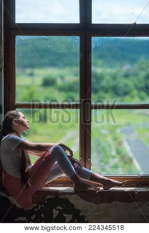 Small child on window sill with summer landscape view. Daydreaming, nap, rest, snooze. Vacation, wanderlust, travel.