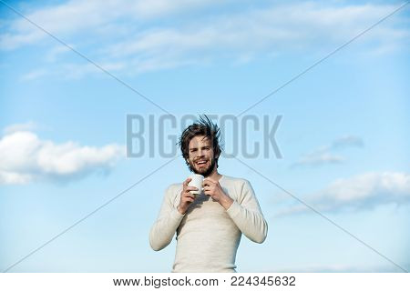 Morning with coffee or milk. Insomnia, refreshment and energy. Happy guy with tea cup on blue sky background. Man with disheveled hair drink mulled wine. Cold and flu, single.