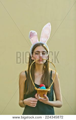 Easter Woman Holding Wicker Basket With Eggs In Mouth. Girl With Rosy Bunny Ears On Beige Background