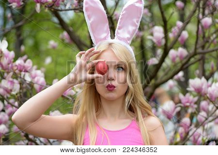 Girl Or Pretty Woman With Long, Blond Hair Making Kissing Lips, Grimace With Red Egg In Rosy, Bunny