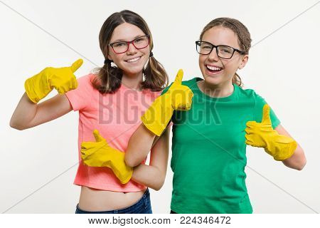Girls teenagers wearing yellow protective gloves show thumbs up. Cleaning time, white background
