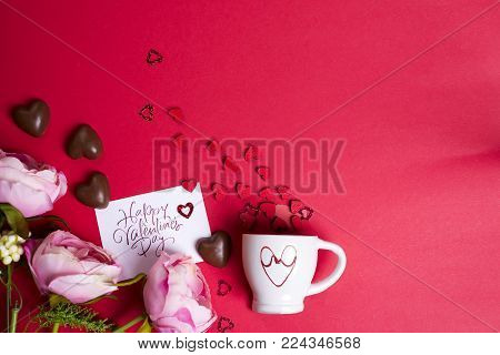 Delicious chocolate candies , flowers with card and cup with wooden hearts on a red background. Greeting card for Mother's Day, 8 March, Birthday, Valentines Day copy space flat lay