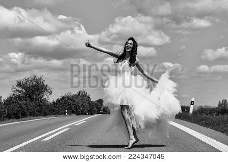 young wedding happy sexy girl or woman with brunette hair and pretty face in white bride dress stop car on road way with thumb up on cloudy blue sky background with green nature