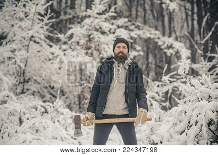 Man lumberjack with ax. Temperature, freezing, cold snap, snowfall. Bearded man with axe in snowy forest. skincare and beard care in winter, beard warm in winter. Camping, traveling and winter rest.