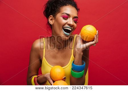 Food fashion photo of joyful mixed-race woman with colorful makeup having fun holding lots of ripe oranges in hands isolated over red wall