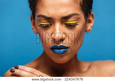 Closeup stylish photo of uptight mixed-race woman with trendy makeup expressing frustration and looking down isolated over blue wall