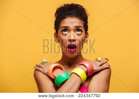 Portrait of shy african woman in colorful adornment with open mouth looking upward crossing hands on shoulders over yellow wall