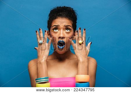 Colorful portrait of woman with stylish makeup emotionally demonstrating jewelry on hands looking upward over blue wall