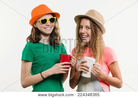 Girlfriends 12-14 years old, on a white background in hats talking, holding cups