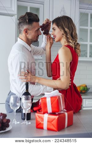 Portrait of a happy romantic smart dressed couple eating grapes while celebrating Valentine's Day on a kitchen at home